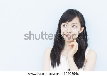 young woman thinking, against pale blue background