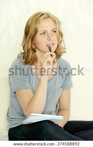 Young woman thinking over making notes in notebook - stock photo