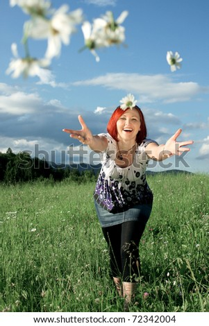 Young woman throwing daisies - stock photo