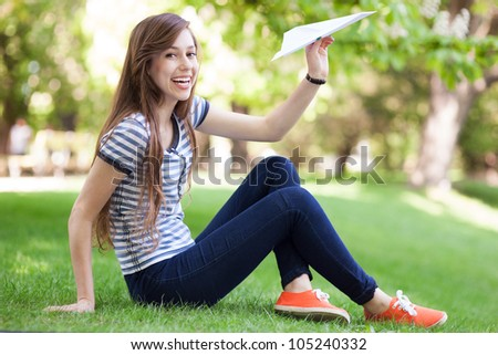 Young woman throwing paper plane - stock photo