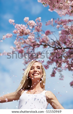 Young woman throwing pink cherry blossoms in the air - stock photo