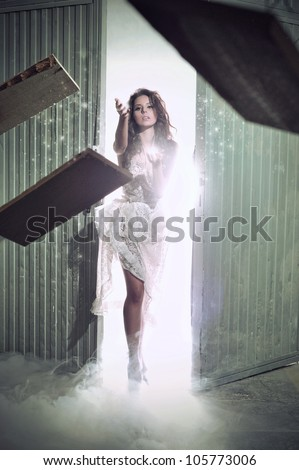Young woman throwing sticks in the smoke - stock photo