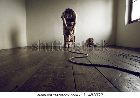 Young woman tied to a chair in a empty room - stock photo