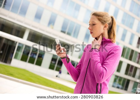 young woman timing her pulse with her phone.  - stock photo