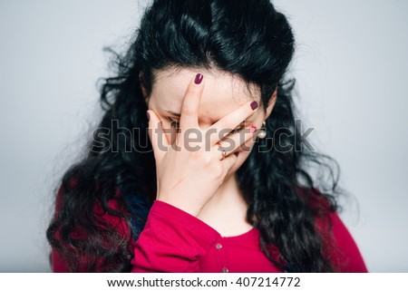 young woman tired and covers his face, dressed in a overalls, close-up isolated on a gray background - stock photo