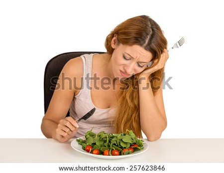 Young woman tired of diet restrictions deciding whether to eat healthy food craving sweet cookies sitting at table isolated white  background. Human face expression emotion. Nutrition concept - stock photo