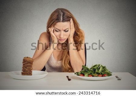 Young woman tired of diet restrictions deciding whether to eat healthy food or sweet cookies she is craving sitting at table isolated grey background. Human face expression emotion. Nutrition concept - stock photo