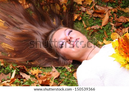 Young woman to lie autumn leaves hand fall yellow maple girl garden background
