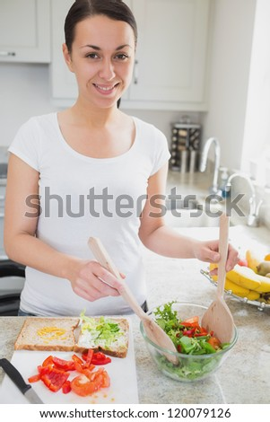 Young woman tossing salad fro sandwich in kitchen