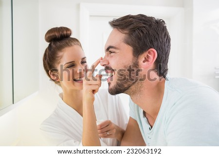 Young woman touching her boyfriends nose at home in the bathroom - stock photo