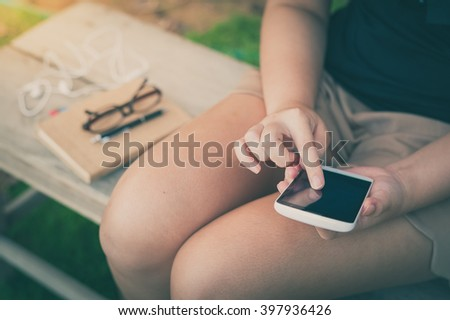 Young woman touching on smartphone screen while sitting on wood bench in park in morning time on weekend with vintage filter effect