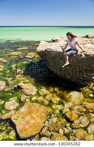 Young woman tourist enjoys the amazing water and rocks