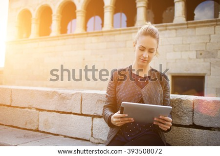 Young woman tourist is reading interesting historical facts on touch pad during a tour in the old town. Female is watching video on digital tablet, while is standing against architectural building - stock photo