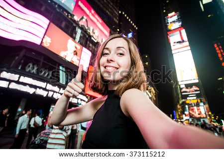 Young woman tourist laughing and taking selfie photo in New York City, Manhattan, Times Square. Female traveler and photographer takes picture for her blog. - stock photo