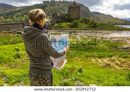 Young woman tourist looks at a road map. In background the famous and spectacular Eilean Donan Castle in Dornie, Kyle of Lochalsh, Scotland, United Kingdom. - stock photo
