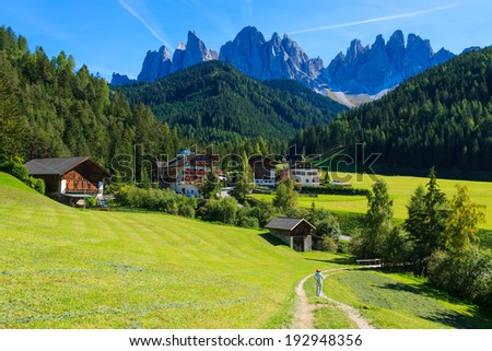 Young woman tourist on rural road in green valley Santa Maddalena village, Val di Funes, Dolomiti Mountains, Italy