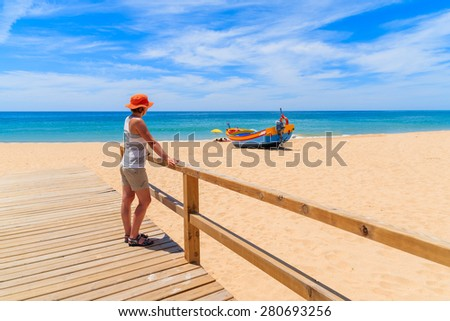 Young woman tourist on wooden footbridge with colorful typical fishing boat on beach in Armacao de Pera coastal village, Portugal