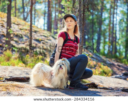 Young woman tourist sitting on stone with dog in summer forest. - stock photo