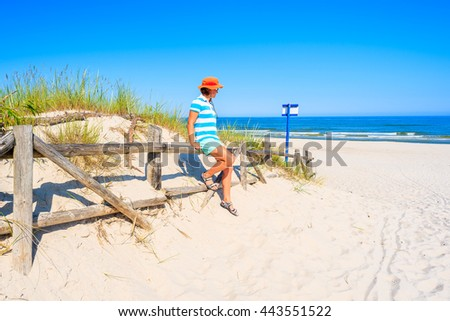 Young woman tourist standing at entrance to beautiful sandy beach in Lubiatowo coastal village, Baltic Sea, Poland