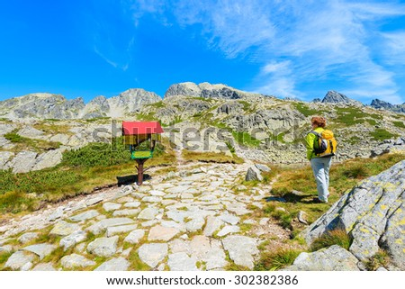 Young woman tourist standing near path with directions sign in Starolesna valley, High Tatra Mountains National Park, Slovakia