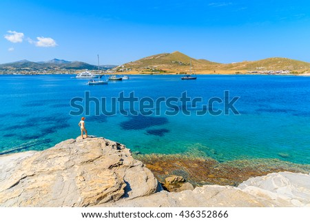 Young woman tourist standing on a rock and looking at beautiful Monastiri bay with turquoise sea water, Paros island, Greece