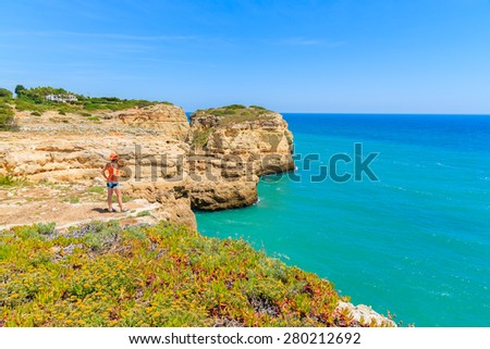 Young woman tourist standing on cliff and looking at turquoise ocean near Carvoeiro town, Algarve region, Portugal