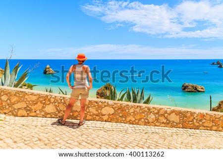 Young woman tourist standing on coastal promenade and looking at beautiful sea near Dona Ana beach, Portugal - stock photo
