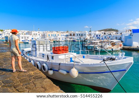 Young woman tourist standing on pier in front of a fishing boat in Naoussa port, Paros island, Greece