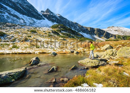 Young woman tourist standing on rock and looking at lake in autumn season, High Tatra Mountains, Poland