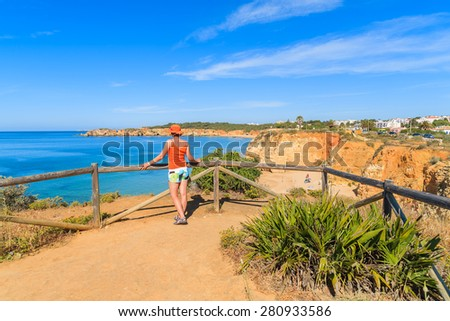 Young woman tourist standing on viewpoint and looking at beautiful Praia da Rocha beach, Portugal