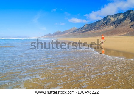 Young woman tourist walking on Cofete beach and volcanic mountains in the background on Jandia peninsula, Fuerteventura, Canary Islands, Spain