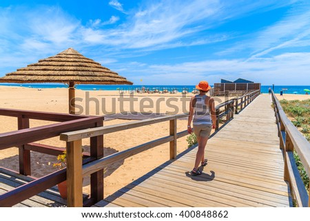 Young woman tourist walking on wooden footbridge to sandy beach in Armacao de Pera coastal town, Algarve region, Portugal