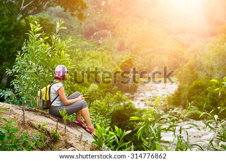 Young woman tourist with backpack relaxing on top of the mountain and enjoying beatiful sunset. Ecotourism concept image, with happy female hiker. - stock photo