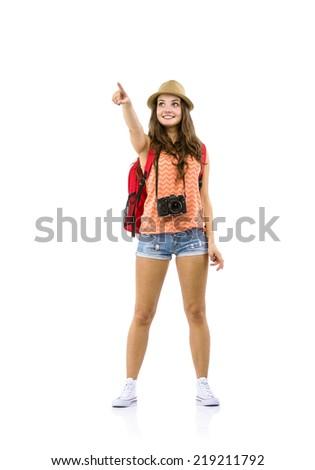 Young woman tourist with camera and backpack pointing somewhere, isolated on white - stock photo