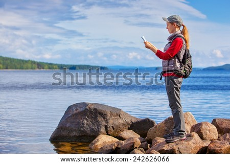 Young woman tourist with map and backpack standing on lake shore. Big rocks and wide lake on background. - stock photo