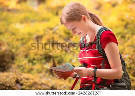 Young woman tourist with map portrait on forest background. - stock photo