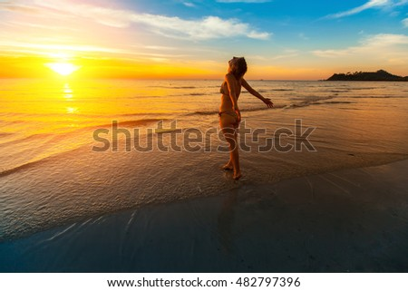 Young woman towards the beautiful sunset on the sea beach.