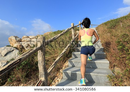 young woman trail runner  stretching legs on mountain trail - stock photo