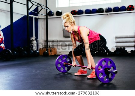 Young woman training deadlift with barbells at gym - stock photo