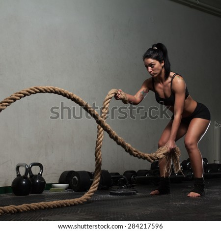 Young woman training in the dark gym  - stock photo