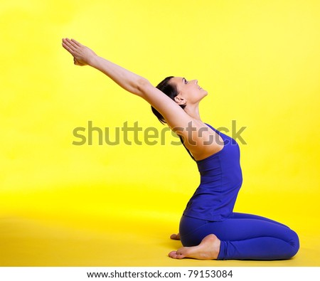 young woman training in yoga asana - pigeon pose on yellow - stock photo