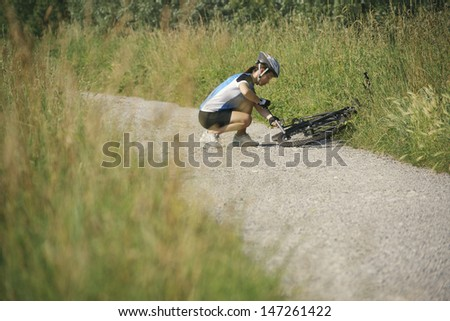 young woman training on mountain bike and repairing flat tyre on track in countryside - stock photo