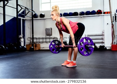 Young woman training Straight Leg Deadlift exercise at gym - stock photo