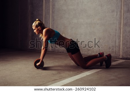 Young woman training with ab wheel - stock photo