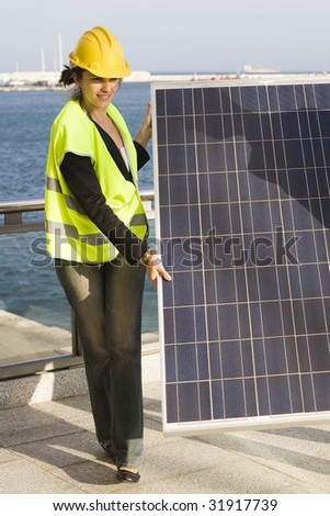 Young woman transporting a solar panel - stock photo