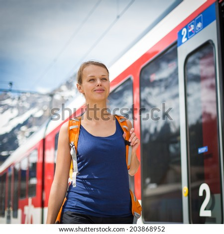 Young woman traveling by train, happy to have reached her destination - stock photo