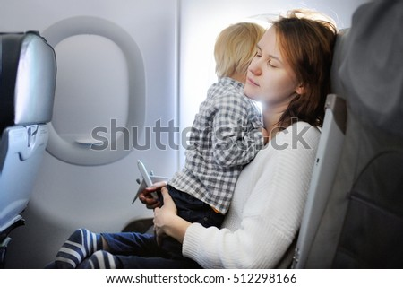 Young woman traveling with her little child by an airplane. Toddler boy sitting with his tired mother by aircraft window. Motherhood concept