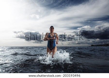 Young woman triathlete running out of cold water to the transition area - stock photo