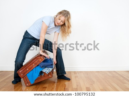 Young woman tries to close a suitcase with too much clothing in it. - stock photo