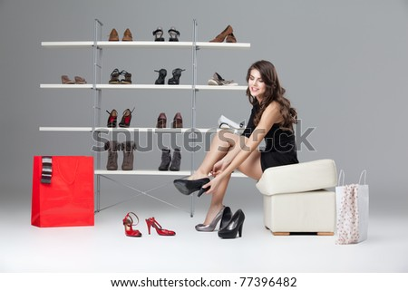 young woman trying on black high heels